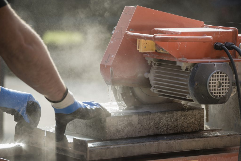 Workman cutting using an angle grinder