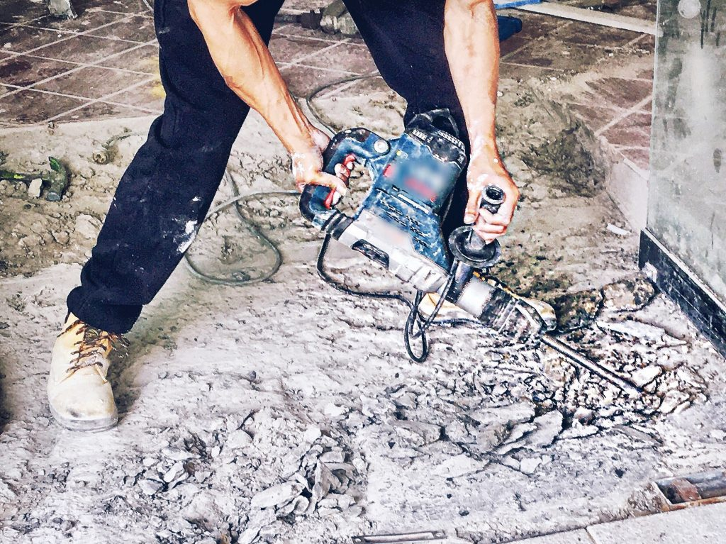 Construction,repairs,damage-close up of builder's hands holding power tool drilling concrete floor