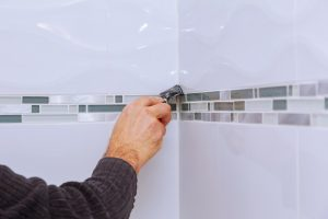 Home improvement renovation applying silicone sealant with construction worker fills seam the