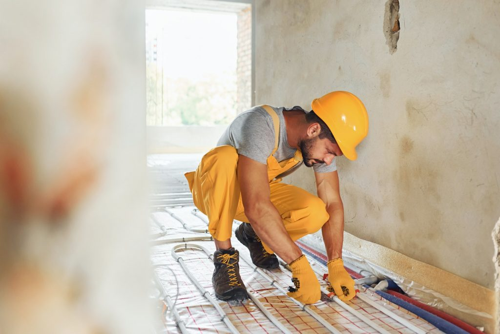Almost done. Worker in yellow colored uniform installing underfloor heating system