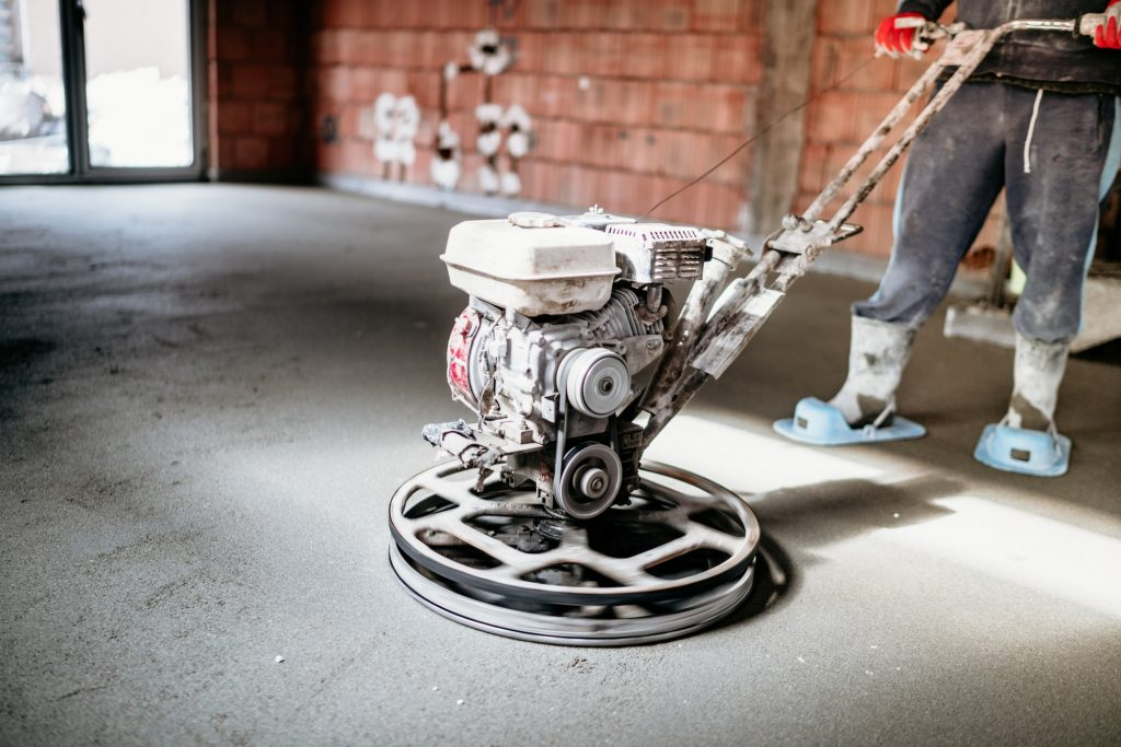Worker with power trowel tool finishing concrete floor, screed, smooth concrete surface